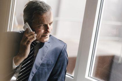 uomo complotta al telefono