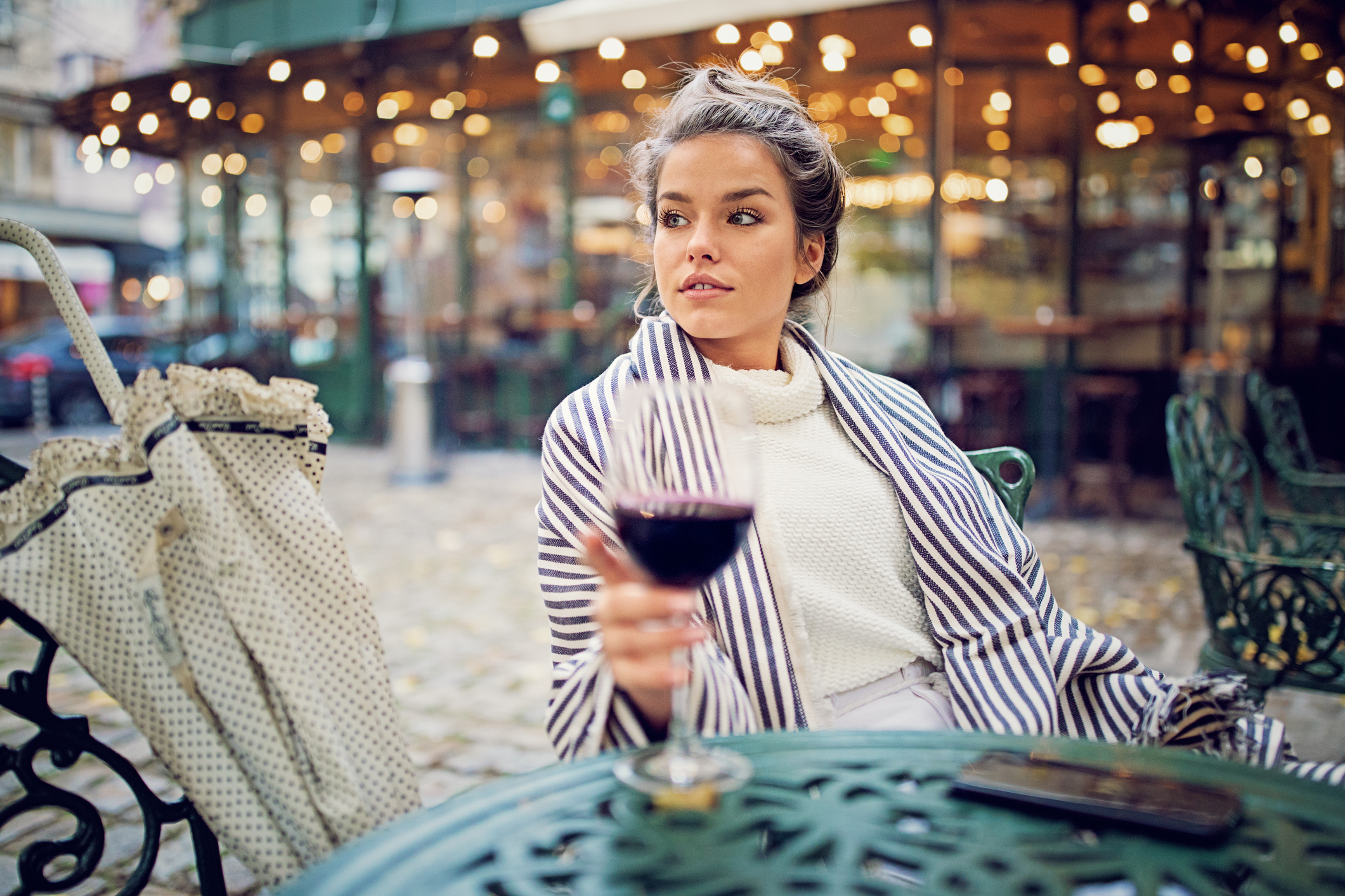 donna beve vino in un bistrot
