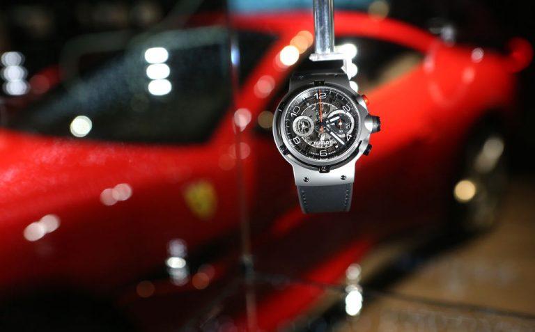 Orologio di lusso, sullo sfondo una Ferrari