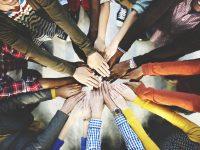 Gruppo di persone si stringe le mani